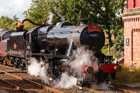 Preserved Stanier Class 8F steam locomotive number 48151 takes on water in Appleby, England, on the Settle to Carlisle railway. Editorial