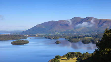 Derwentwater View.  A view across Derwentwater in the English Lake District national park to the town of Keswick and beyond is Skiddaw.  Skiddaw is the fourth highest mountain in England. Stock Photo