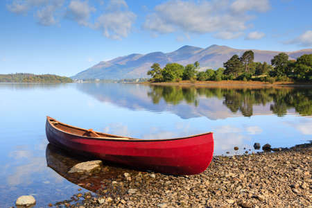Red Canoe.  A red canoe on the banks of Derwentwater in the English Lake District National Park.  Skiddaw, the fourth highest mountain in England, can be seen in the background. Stockfoto - 101170888