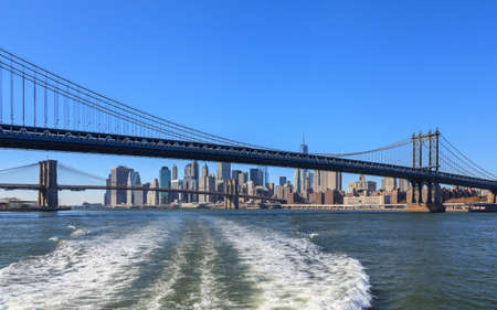 East River.  A view back along the East River in New York City to the Manhattan Bridge.  Beyond is Brooklyn Bridge and the New York City skyline. Stock Photo - 85486173