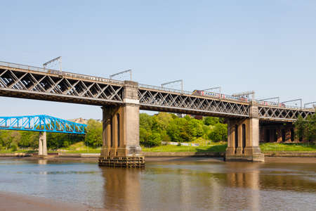 The King Edward VII bridge over the River Tyne in North East England.  A train is seen crossing between Newcastle upon Tyne and Gateshead. 報道画像