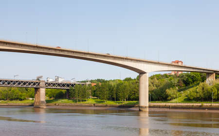Traffic is seen crossing Redheugh Bridge over the River Tyne and in the background is the King Edward VII railway bridge.  The bridges connect Newcastle upon Tyne and Gateshead.
