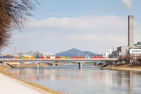 The view along the Salzach River in Salzburg, Austria as a freight train crosses the railway bridge