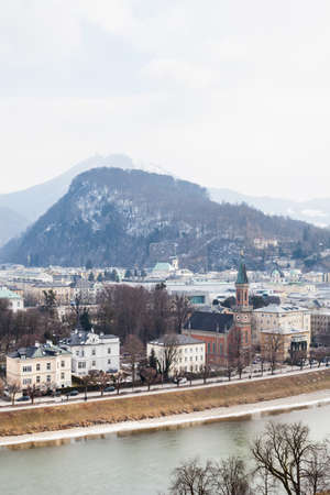 A winter view across the Salzach River and Salzburg skyline in Austria.  In the background can be seen Kapuzinerberg, a hill on the eastern banks of the Salzach river, 写真素材