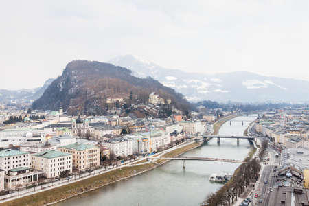 A winter view across the Salzach River and Salzburg skyline in Austria.  In the background can be seen Kapuzinerberg, a hill on the eastern banks of the Salzach River,