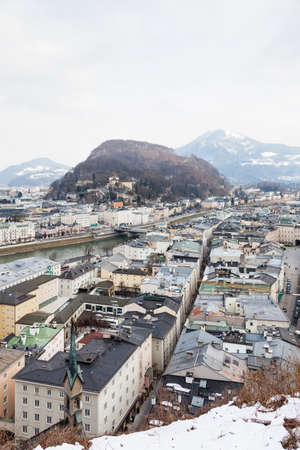 A winter view across the Salzach River and Salzburg skyline in Austria.  In the background can be seen Kapuzinerberga a hill to the east of the Salzach River.