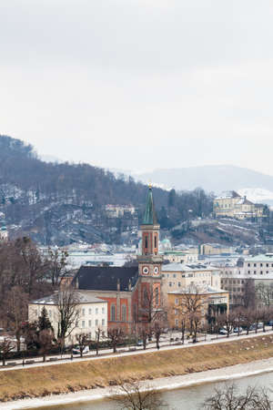 A winter view across the Salzach River, Salzburg in Austria.  In the foreground is the Protestant parish Salzburg Christ Church.
