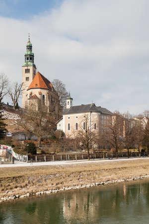 A view across the Salzach River in Salzburg, Austria.  In the background is the the parish church Mulln, a Roman Catholic church.