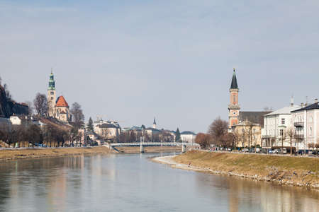 The view along the Salzach River in Salzburg, Austria looking towards the Mullner Steg Bridge.  In the background can be seen the parish church Mulln and the protestant parish Christ Church. 報道画像