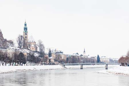 A mid winter view along the Salzach River in Salzburg, Austria looking towards the Mullner Steg Bridge and the parish church Mulln, a Roman Catholic church.