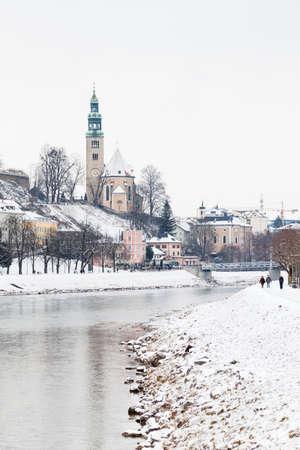 A mid winter view along the Salzach River in Salzburg, Austria.  In the background can be seen the Mullner Steg Bridge and the parish church Mulln, a Roman Catholic church.