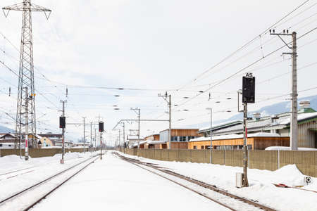 The view along a snow covered railway track from Bruck - Fusch Station in the state of Salzburg, Austria.  Bruck and Fusch are both municipalities in Zell am See district.