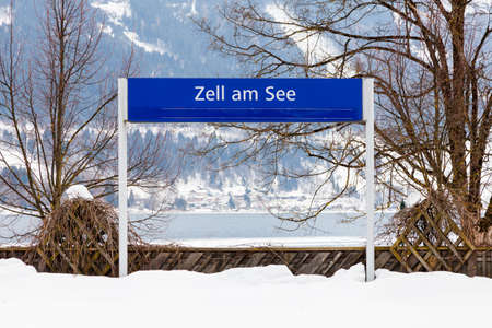 The destination sign for Zell am See Station.  Zell am See is a town in the state of Salzburg, Austria.  In the background can be seen Lake Zell.