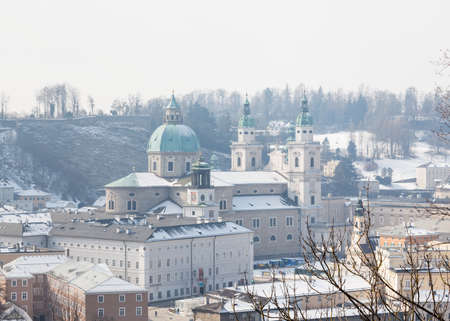 A winter view across the Salzach river from Kapuzinerberg mountain in Austria.  Salzburg Cathedral in the