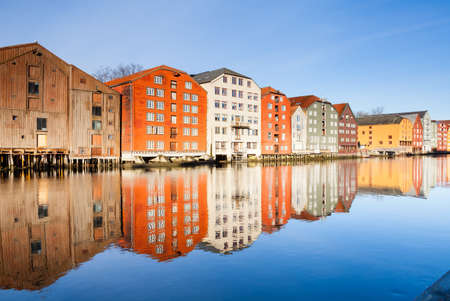 Old wooden storehouses beside the Nidelva River in Trondheim, Norway.