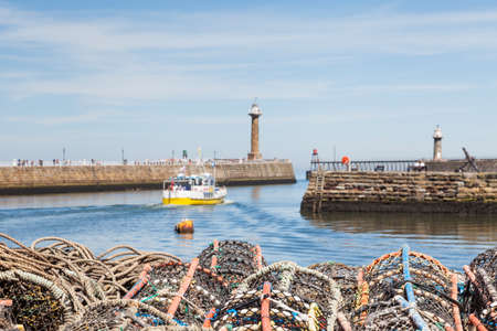 The view across lobster fishing pots stacked on the keyside of the seaside town of Whitby in Yorkshire, Northern England.