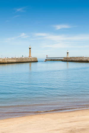 The east and west piers at the entrance to the seaside town of Whitby in Yorkshire, Northern England as a boat enters the harbour. Redactioneel
