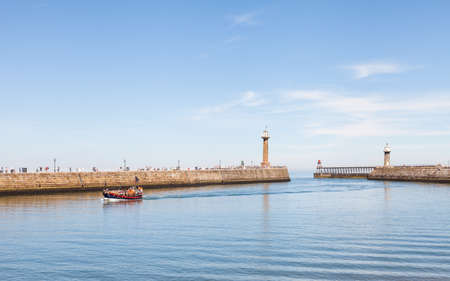 The east and west piers at the entrance to the seaside town of Whitby in Yorkshire, Northern England as a tourist boat arrives in the harbour. Redactioneel