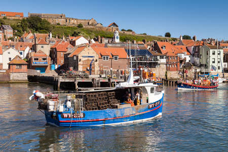 A fishing boat laden with lobster pots arrives in the seaside town of Whitby in Yorkshire, Northern England. Redactioneel
