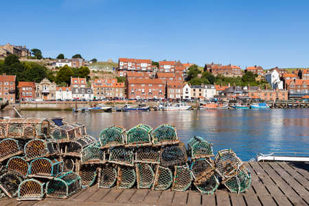 The view across lobster fishing pots stacked on the keyside of the seaside town of Whitby in Yorkshire, Northern England. Redactioneel