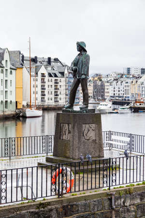 A fisherman statue beside the Alesund waterfront in Norway.  Alesund is a port town on the west coast of Norway. Redactioneel