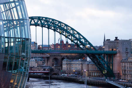 An evening view past the Sage towards the Tyne Bridge and Newcastle upon Tyne, England.  The bridge spans the River Tyne and connects Gateshead and Newcastle upon Tyne. Redactioneel