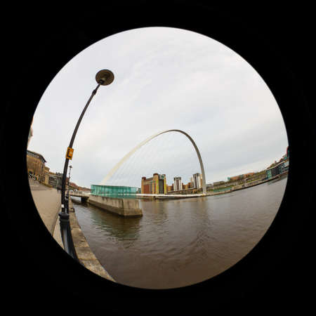 A fish eye view of the Gateshead Millennium Bridge.  The bridge connects Newcastle upon Tyne and Gateshead in north east England.  In the background is the Baltic Centre for Contemporary Art, a converted flour mill on the banks of the River Tyne.