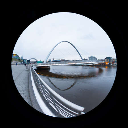 An early evening fish eye view of the Gateshead Millennium Bridge.  The bridge connects Newcastle upon Tyne and Gateshead in northern England.  In the background can be seen the Tyne Bridge and the Sage.  The Sage is a centre for musical education and per Redactioneel