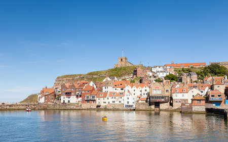 The View Across the River Esk in the Town of Whitby in North Yorkshire, England.  St Mary's Church overlooks the town from the top of the east cliff.