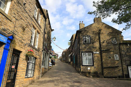 The view looking up the cobbled main street in Haworth, West Yorkshire, England.  Haworth was home to the Bronte sisters and is a popular tourist destination. Redactioneel