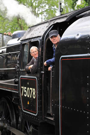 A close up of the driver and fireman on steam train 75078.  The train prepares to depart Haworth Station on the Keighley and Worth Valley Railway, England.