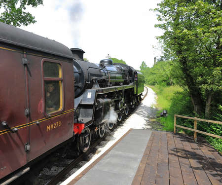 A steam train departs Haworth Station, on the Keighley and Worth Valley Railway, England.  The railway was used in the film the Railway Children.