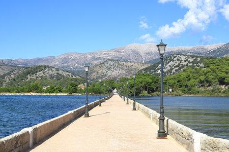 De Bosset Bridge. The view along De Bosset Bridge (formerly Drapano Bridge) on the Greek island of Kefalonia. The bridge spans Koutavos Lagoon in Argostoli.