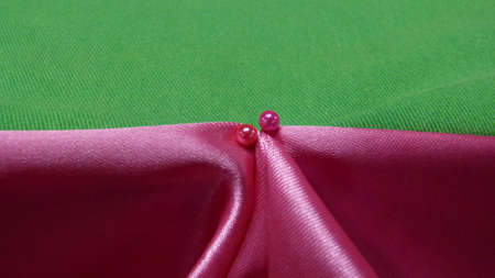 predominant: Notable pin head on pink and green satin