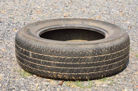 sleeping car: Old black tire on rock road