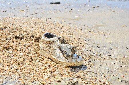disused: Old disused shoe on broken shell beach