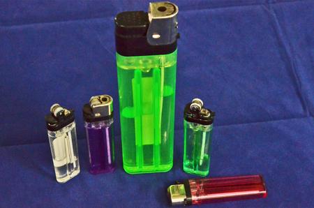 encendedores: Encendedores de plástico de colores sobre fondo azul