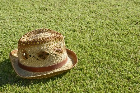 upturn: Brown textile hat on the green grass Stock Photo