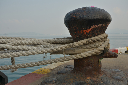 tether: Old big cleat with ropes to hold a ship