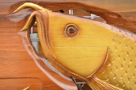 asian arowana: Graven arowana fish head on the wood