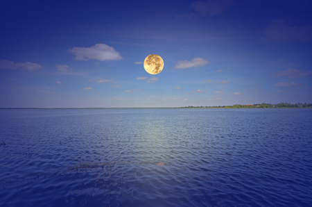 Beautiful full moon over the water Stock Photo