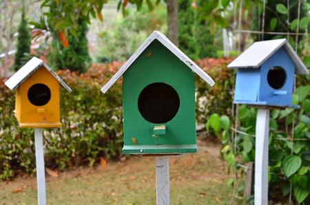 Stock Photo   Three Colored Birdhouses In The Garden