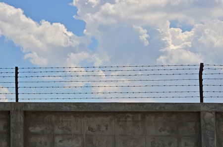 float cotton cloud: Concrete wall with barbed wires on cloudy sky