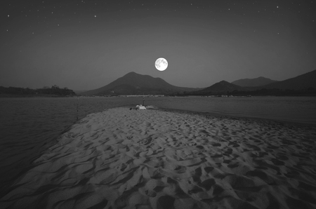 concave: Full moon over the beach in the evening