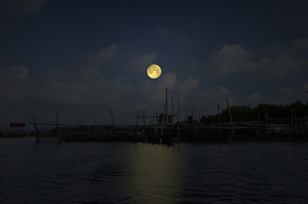 Beautiful full moon over village and water