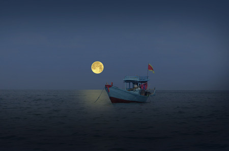 Lonely fisherman boat with full moon evening