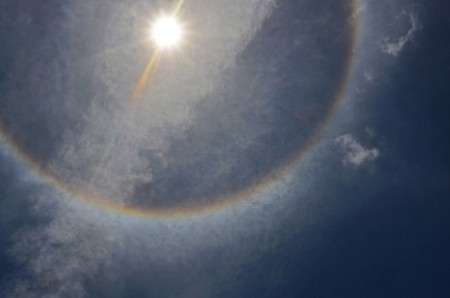 Color sun halo ring at noon on cloudy sly