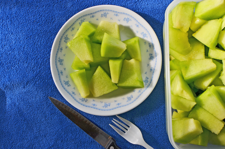 Fresh green fruit of melon dish on blue floor Stock Photo