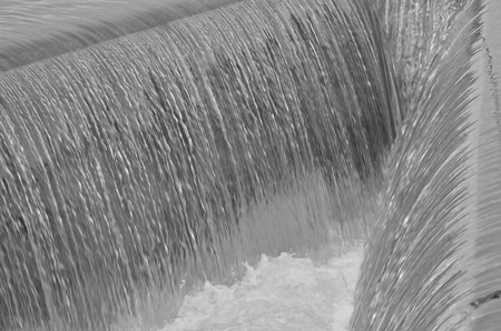 Black and white image of water at side channel spillway