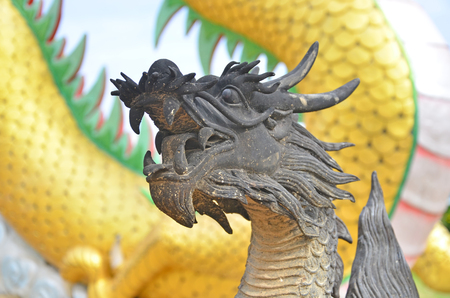 Black dragon sculpture with yellow body background Stock Photo